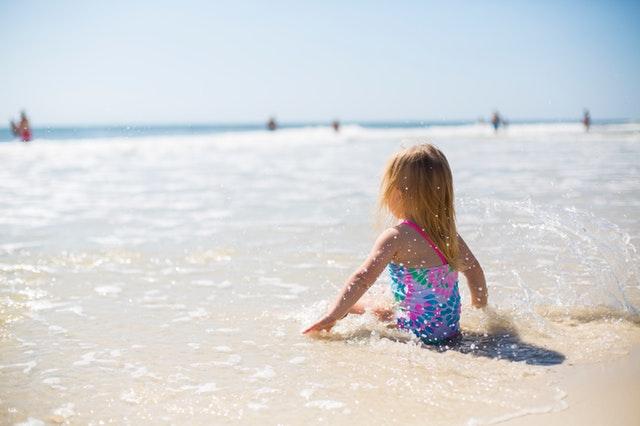 Dievčatko vo farebných plavkách sedí na pláži a hrá sa v mori.jpg