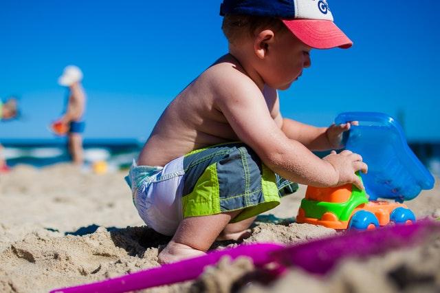 Malý chlapček sa hrá s hračkami a formičkami v piesku na pieskovej pláži.jpg