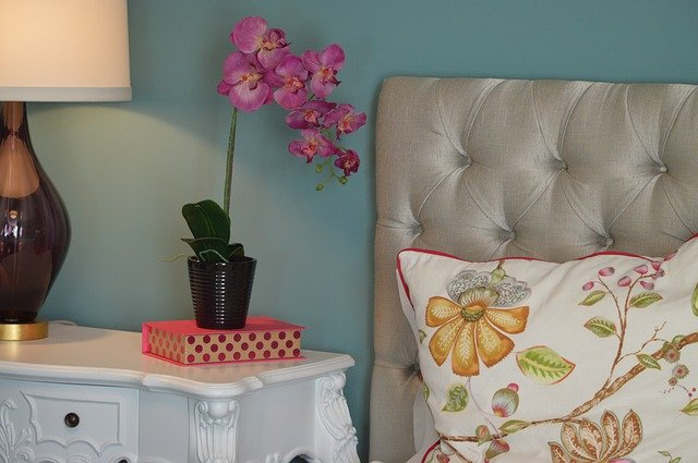 Posteľ s čalúnením a historický nočný stolík s ružovou orchideou.jpg