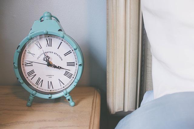 Modrý budík položený na drevenom nočnom stolíku vedľa postele.jpg